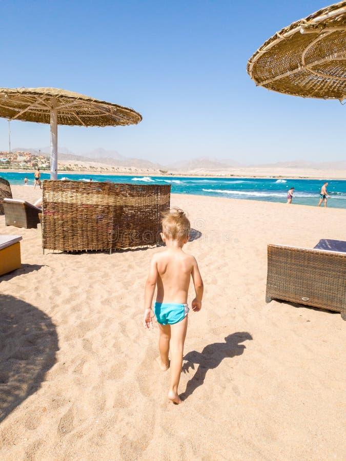 走到海和看海浪的逗人喜爱的小男孩 孩子放松和有美好时光在夏天休假期间 免版税库存图片