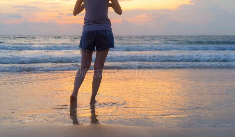 走到海滩的妇女在旅行假日期间在海洋或自然海假期户外在日落时间,普吉岛,泰国 库存图片