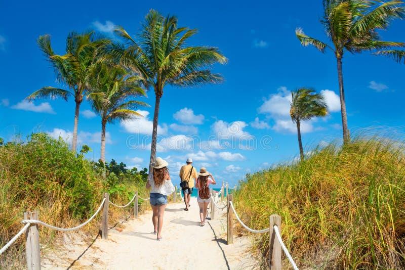 走到海滩的家庭在度假暑假 免版税库存图片