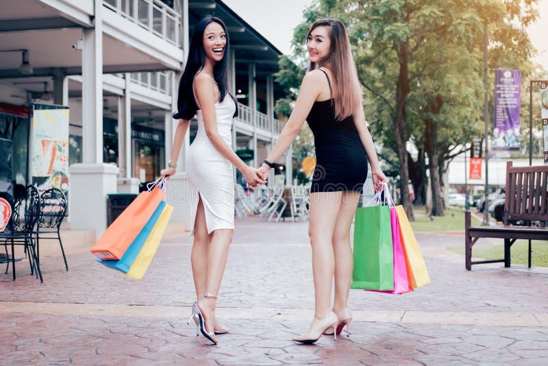 走到购物的两名亚裔妇女背面图在出口m 免版税库存图片