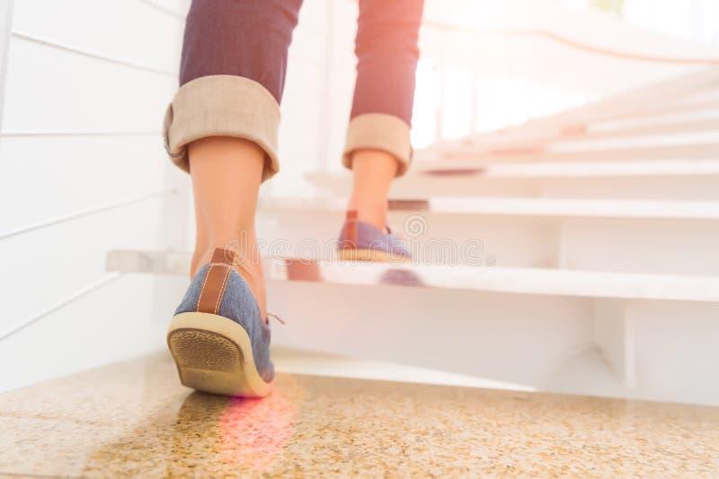 走台阶的年轻妇女有太阳体育背景 免版税库存照片