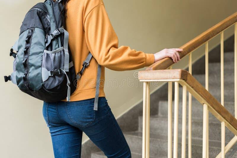 走台阶的年轻无法认出的沮丧的孤独的女性大学生在她的学校 图库摄影