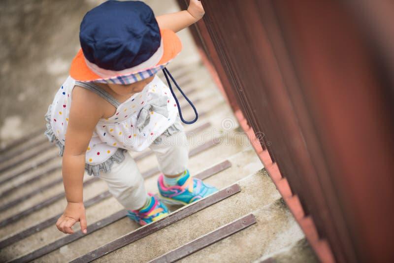 走台阶的愉快的矮小的逗人喜爱的女孩 免版税库存图片