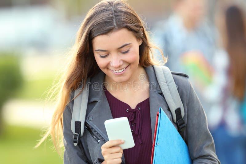 走向照相机的学生使用电话 免版税库存图片