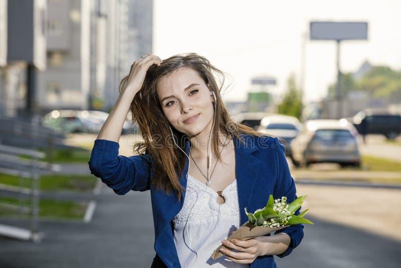 走听到在耳机的音乐的美丽的妇女通过街道有花束的 库存照片