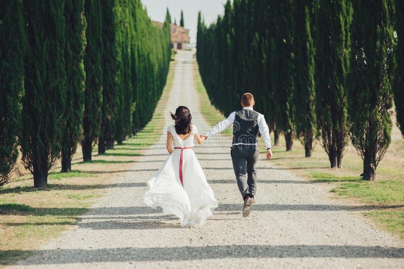走和亲吻在托斯卡纳, Ita的愉快的时髦的微笑的夫妇 免版税库存照片