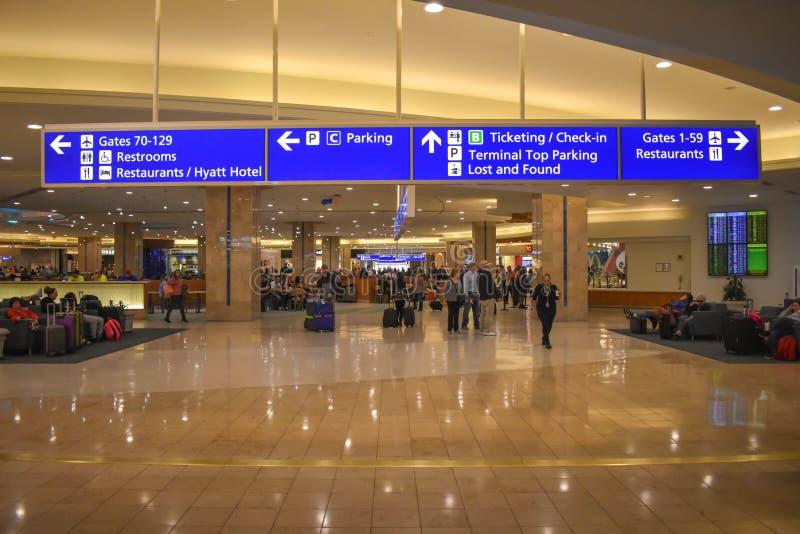 走和休息与bagagges的人们 在奥兰多国际机场的门,停车处,卖票和报到标志 免版税库存照片