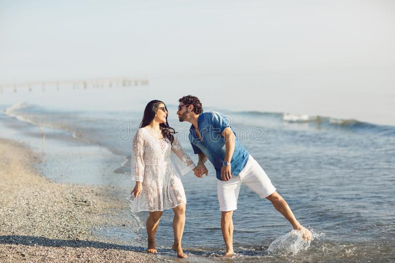 走和使用在海滩的愉快的夫妇,浸泡他的脚在水中 美妙的爱情故事在里米尼,意大利 免版税库存照片