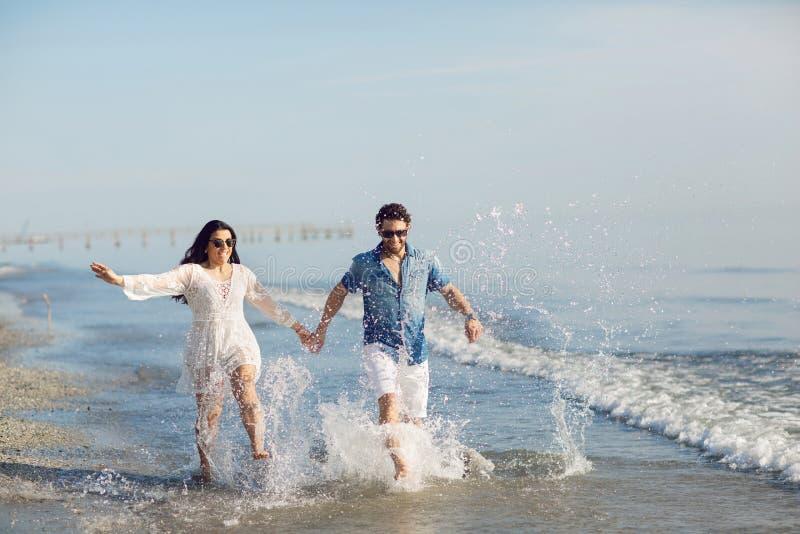 走和使用在海滩的愉快的夫妇,浸泡他的脚在水中 美妙的爱情故事在里米尼,意大利 免版税库存图片