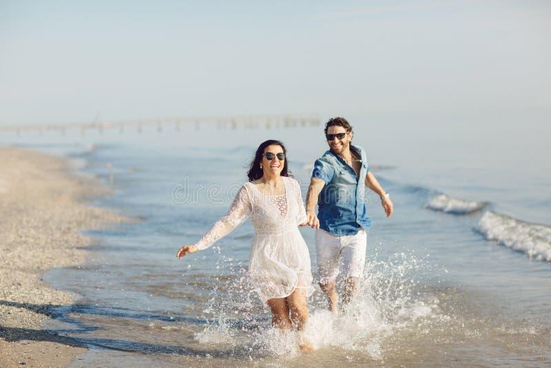 走和使用在海滩的愉快的夫妇,浸泡他的脚在水中 美妙的爱情故事在里米尼,意大利 图库摄影