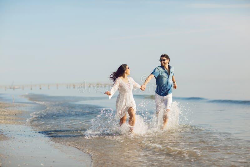 走和使用在海滩的愉快的夫妇,浸泡他的脚在水中 美妙的爱情故事在里米尼,意大利 库存图片