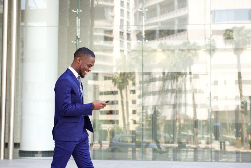 走和使用手机的年轻商人 免版税库存照片