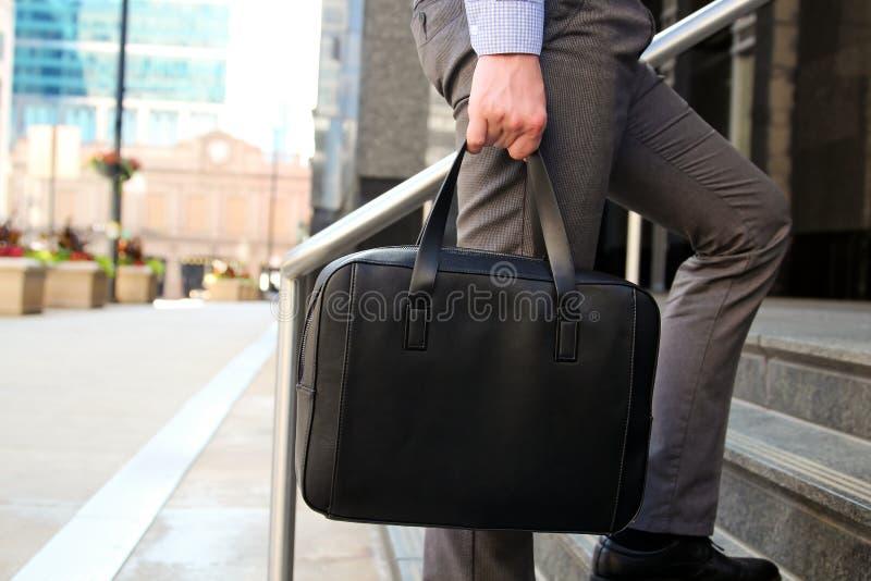 走和拿着一个皮革公文包的商人在他的handss现代城市后边 图库摄影