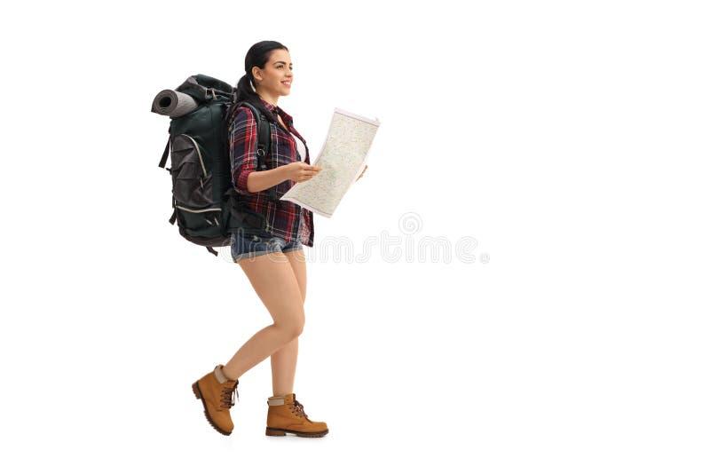 走和拿着一张普通地图的女性远足者 免版税库存图片