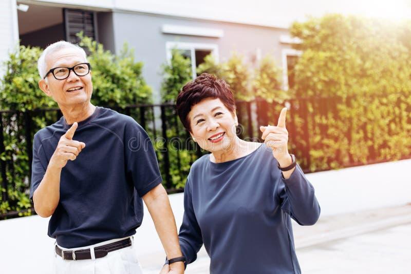 走和指向在室外公园和房子的愉快的资深亚洲夫妇 与阳光的温暖的口气 免版税图库摄影