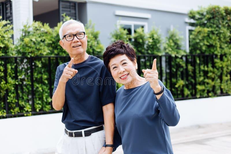走和指向在室外公园和房子的愉快的资深亚洲夫妇 图库摄影