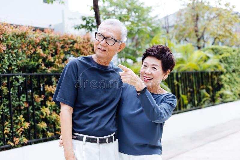 走和指向在室外公园和房子的愉快的资深亚洲夫妇 免版税库存照片