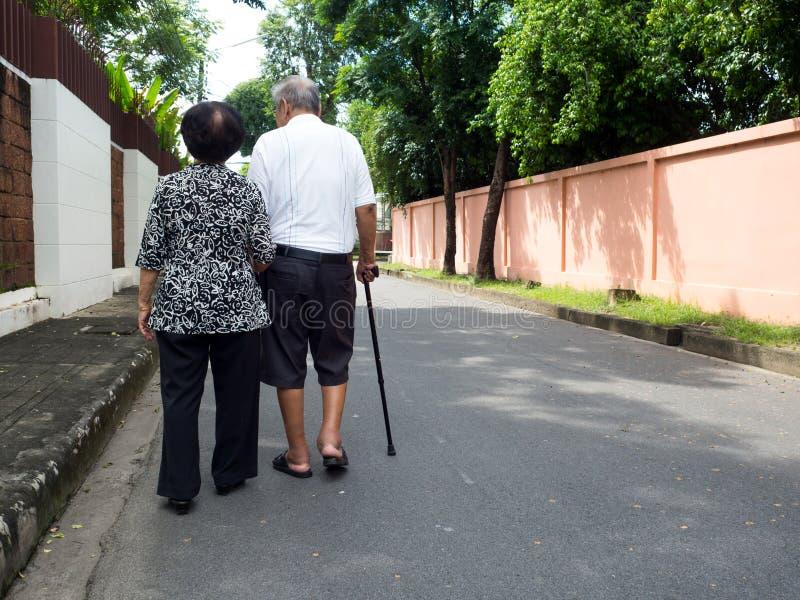 走和握在路的愉快的浪漫资深亚洲夫妇手在村庄 资深夫妇的概念和保重 免版税图库摄影