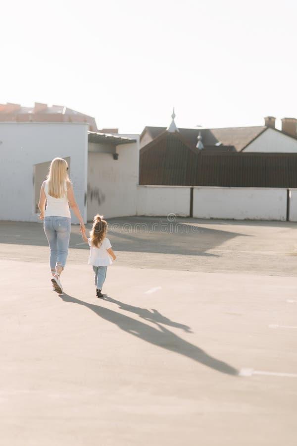 走和握手的妈妈和她的女儿 库存图片