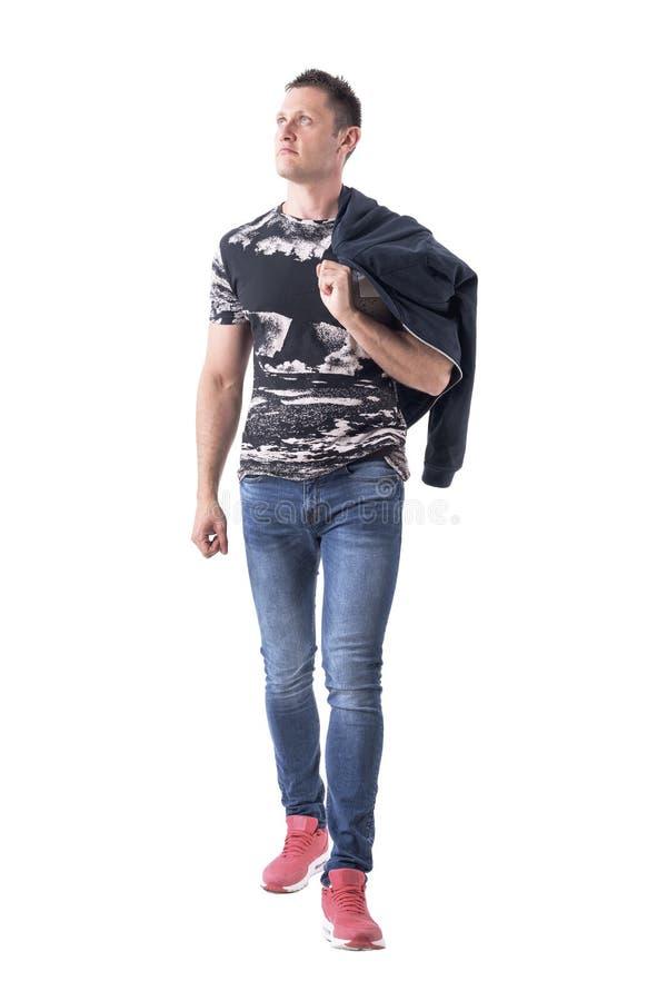 走和查找在肩膀的确信的轻松的偶然年轻人运载的夹克 库存图片