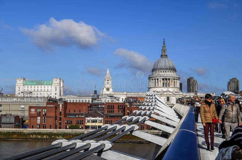 走和横渡千禧桥和圣保罗座堂在背景中,伦敦,英国,英国的游人 库存图片