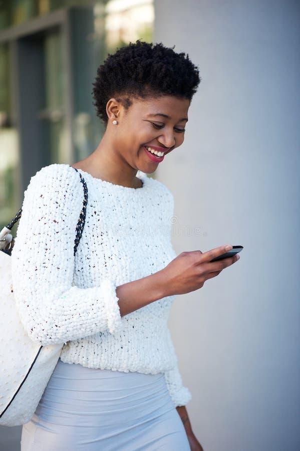 走和看手机的妇女外面 免版税图库摄影