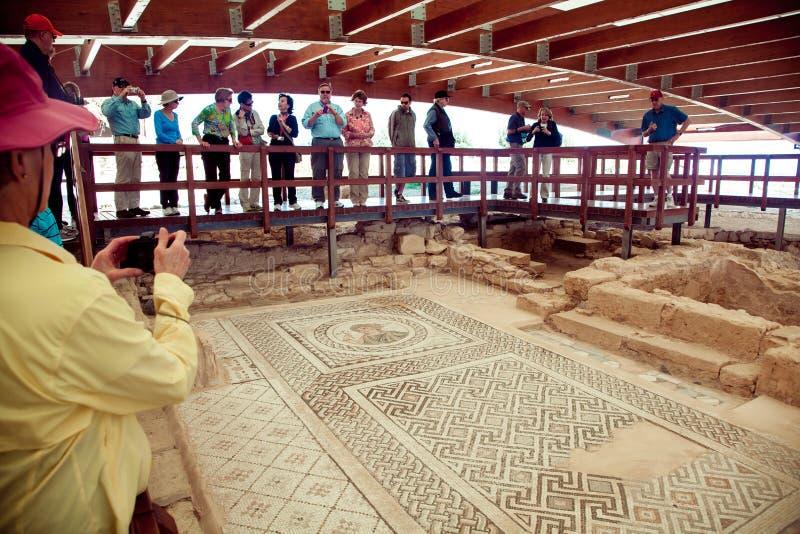 走和观看古老地板马赛克的游人 Kourion是塞浦路斯的西南海岸的一个古城 免版税库存图片