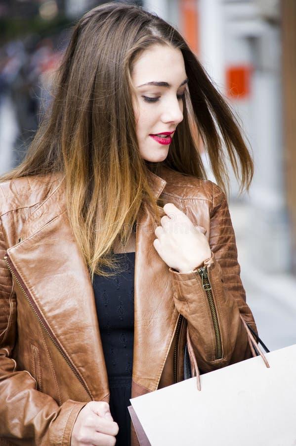 走和购物在城市的愉快的少妇 看商店窗口的时髦女消费者 免版税库存照片