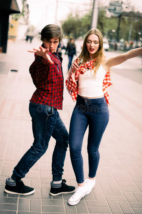 走和跳舞在城市的两个愉快的时髦少年朋友,听到与耳机的音乐,谈和s 库存图片