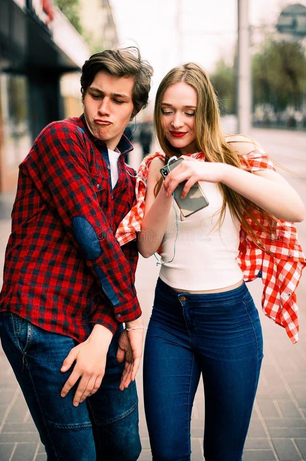 走和跳舞在城市的两个愉快的时髦少年朋友,听到与耳机的音乐,谈和s 免版税库存图片