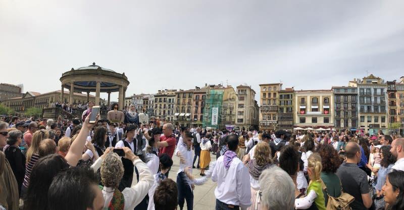 走和跳舞在plaza del castillo在潘普洛纳,Navarra的人们 免版税库存照片