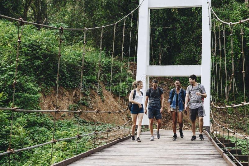 走在一个热带乡下冒险和旅途概念的桥梁的小组朋友 库存照片