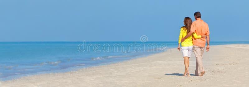 走在一个空的海滩的全景横幅夫妇 库存照片