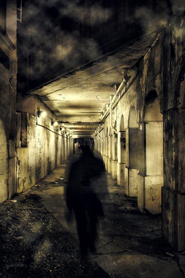 走在一个黑暗的城市隧道的一个可怕鬼魂 免版税库存图片