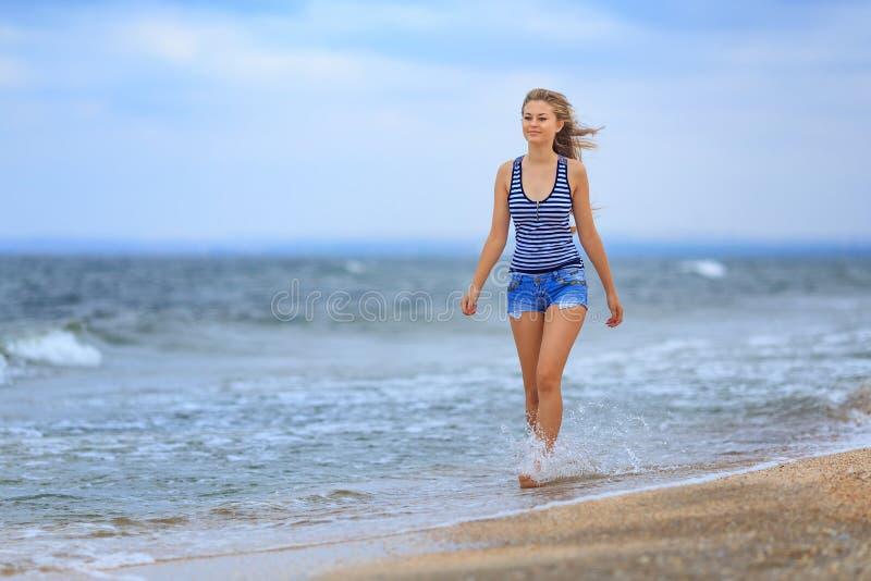 走在一件镶边T恤杉和牛仔布短裤,振翼在风的头发的海滩的美丽的愉快的女孩 免版税图库摄影