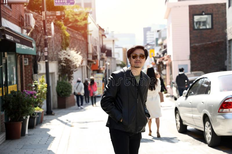 走在一条步行街道上的人佩带的太阳镜黑皮夹克 库存图片