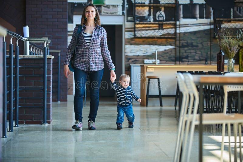 走在与他的妈妈的咖啡馆的小孩 母亲由手采取儿子 库存图片