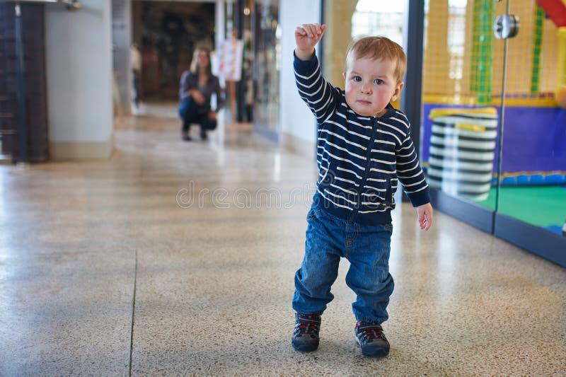 走在与他的妈妈的购物中心的小孩背景的 免版税库存照片
