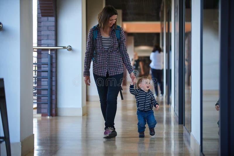 走在与他的妈妈的购物中心的小孩 母亲由手采取儿子 免版税库存图片