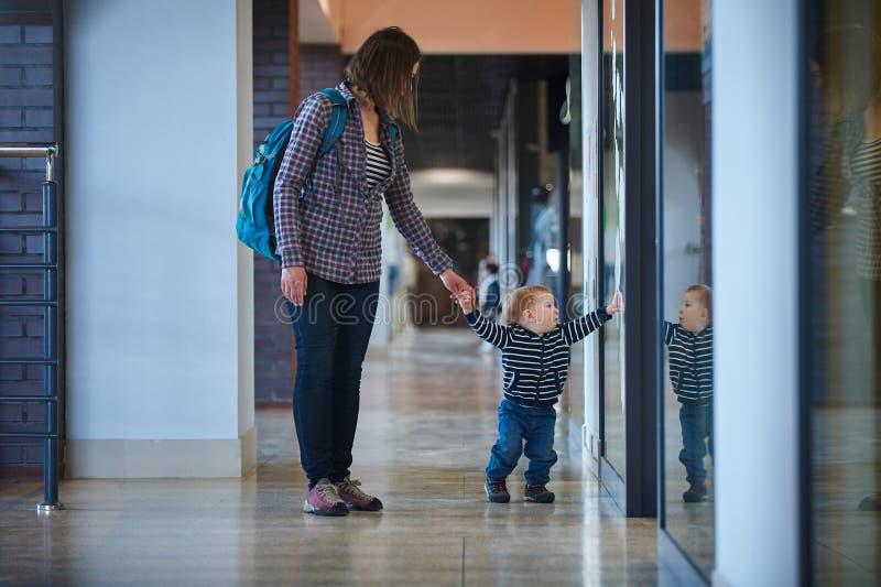 走在与他的妈妈的购物中心的小孩 母亲由手采取儿子 库存照片
