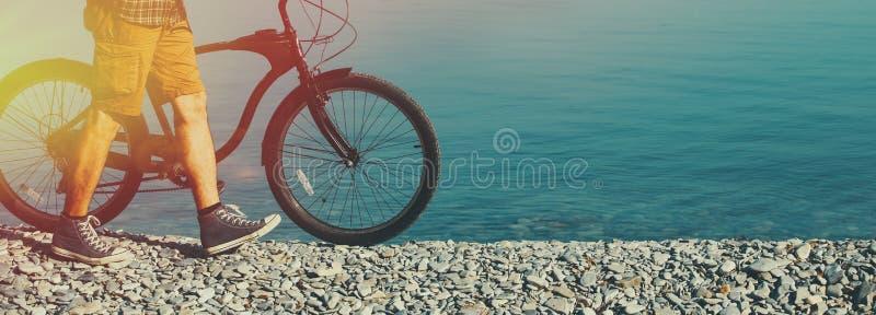 走在与他的自行车的海岸早晨的无法认出的远足者人 免版税库存图片