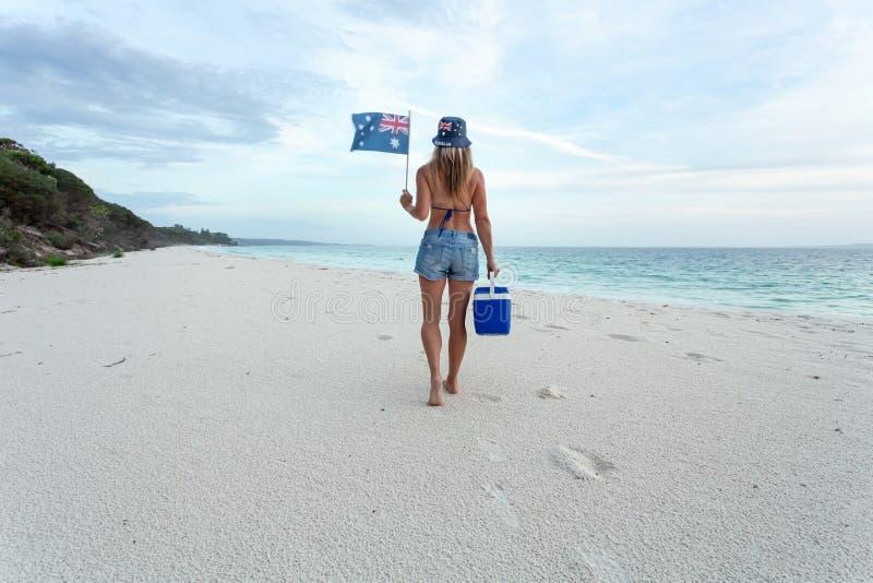 走在与冷饮保藏盒的海滩的澳大利亚海滩文化妇女 免版税库存照片
