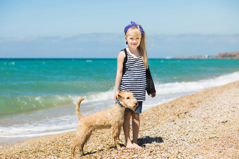 走在与小狗狗的海滩的小女孩 免版税库存图片