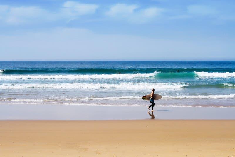 走在与水橇板的晴朗的海滩的冲浪者 免版税库存照片