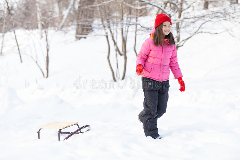 走在与爬犁的雪的女孩 图库摄影