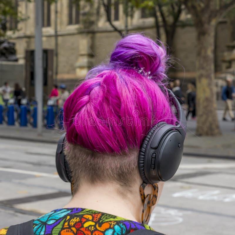 走在与耳机的市中心的年轻女人的异常的头发在她的头 图库摄影