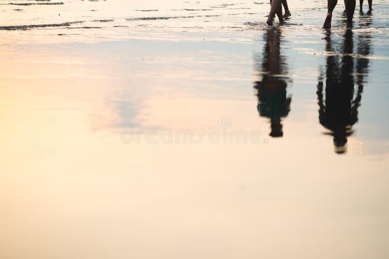 走在与被反射的下落阴影的海滩的夫妇剪影  免版税库存图片