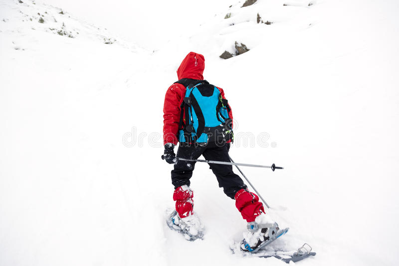走在与雪靴的山的男孩 免版税库存照片