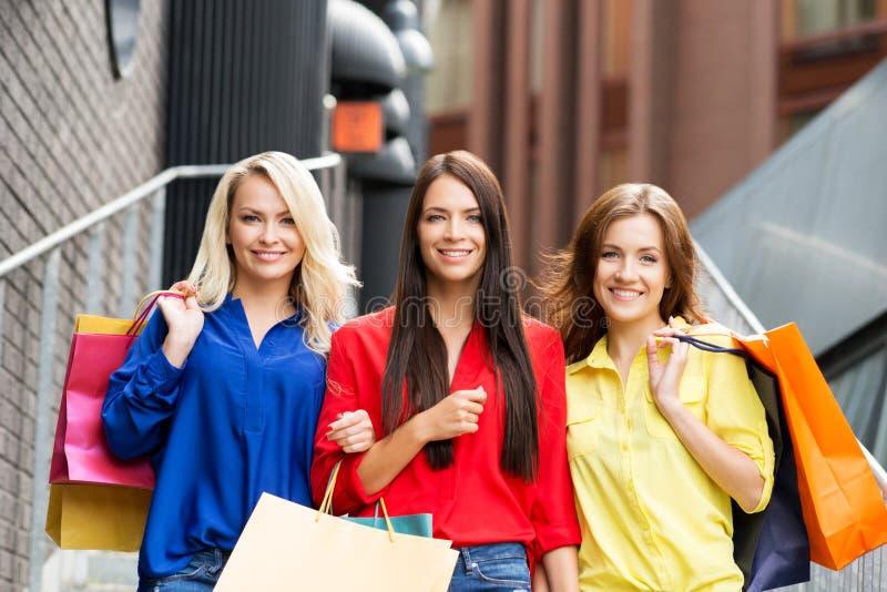 走在与购物袋的市中心的三个可爱的愉快的女性朋友 免版税库存照片