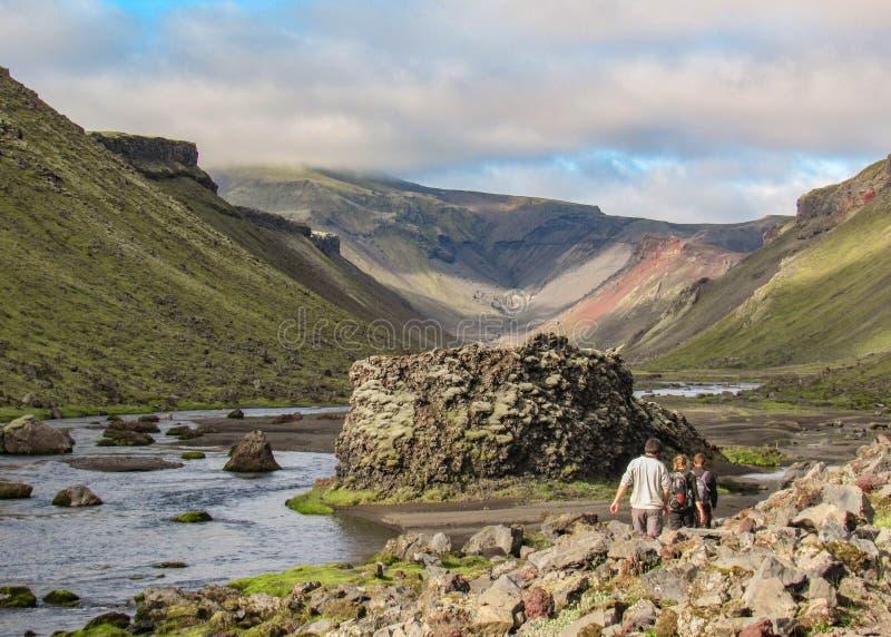 走在世界的最大的火山的峡谷Eldgja,冰岛中部的三个徒步旅行者 免版税图库摄影